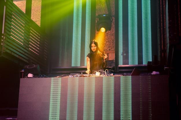 Dj auf der bühne im disco-nachtclub, der techno-musik-beat mischt