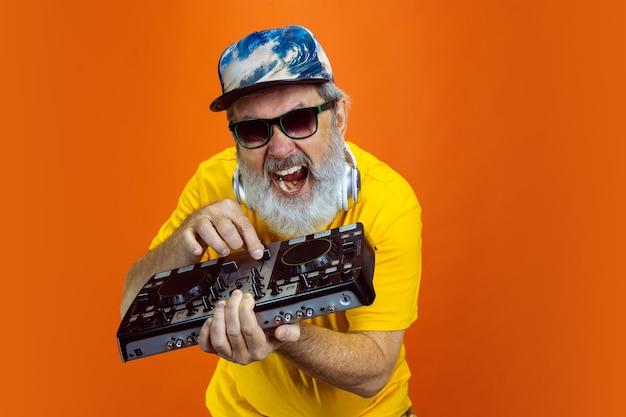 Dj ausrüstung. porträt des älteren hippie-mannes, der geräte verwendet, geräte lokalisiert auf orange studiohintergrund. tech und fröhliches lifestyle-konzept für ältere menschen. trendige farben, ewig jugend. copyspace für ihre anzeige.