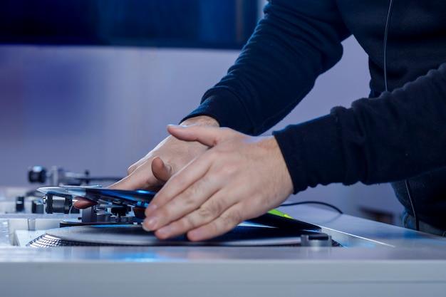 Dj colocando un disco de vinilo en su tocadiscos mientras mezcla msica en una tienda de discos