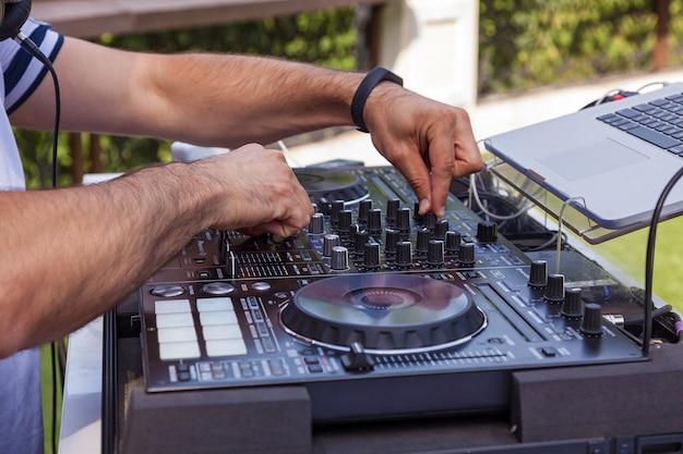Dj-geräte zum anfassen. dj-plattenspieler-mixersteuerung mit zwei händen im konzert
