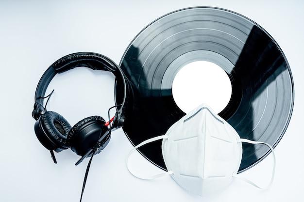 Dj-kit: eine ffp2-maske, kopfhörer, eine schallplatte, die nach dem coronavirus 2019 in diskotheken gespielt werden kann.