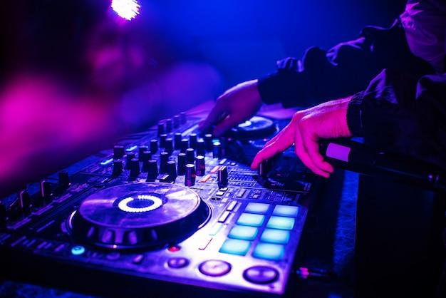 Dj-konsole zum mischen von musik mit händen und mit verschwommenen menschen, die auf einer nachtclubparty tanzen