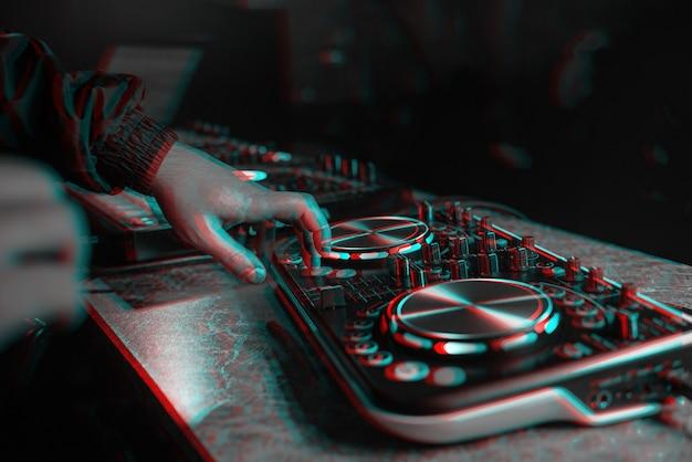 Dj-konsole zum mischen von musik mit händen und mit verschwommenen menschen in einem nachtclub. schwarzweiß mit 3d-glitch-virtual-reality-effekt