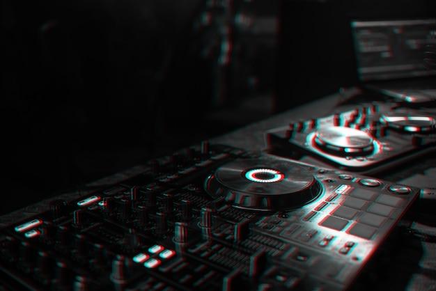 Dj-konsole zum mischen von musik mit verschwommenen leuten, die auf einer nachtclubparty tanzen. schwarzweiß mit 3d-glitch-virtual-reality-effekt
