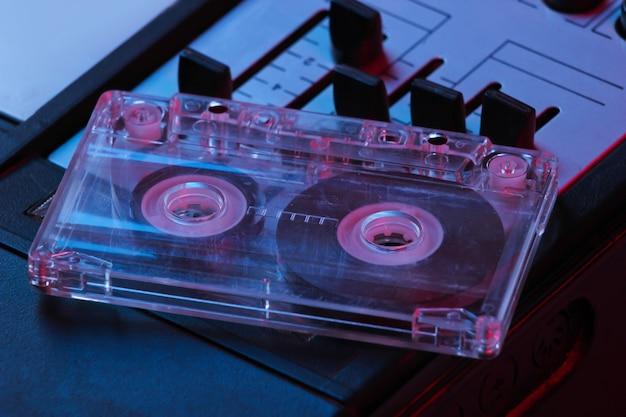 Dj-konsolentuner mit audiokassette in pinkblauem neonlicht