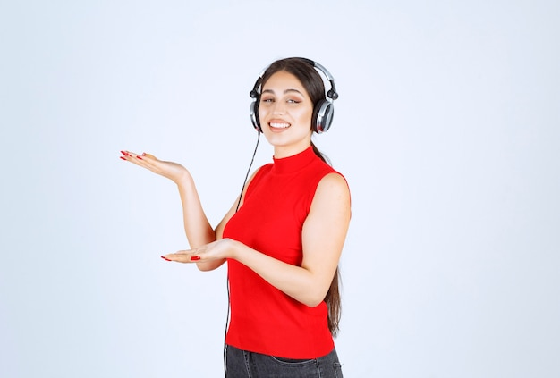 Dj-mädchen im roten hemd mit kopfhörern, die etwas zeigen oder etwas in ihrer hand zeigen.