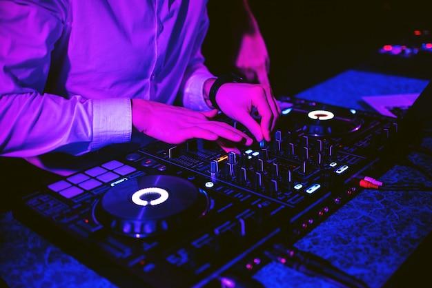 Dj mischt elektronische musik mit seinen händen auf einem musikcontroller