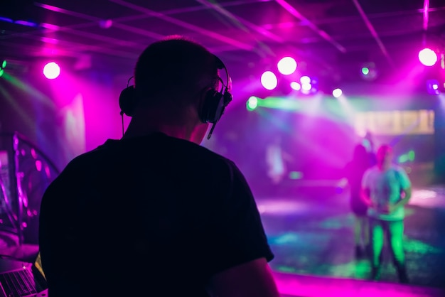 Dj mischt musik in einem nachtclub mit den leuten, die tanzen