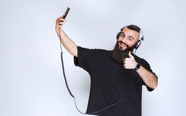 Dj mit bart trägt kopfhörer, öffnet die smartphone-kamera und macht sein selfie.