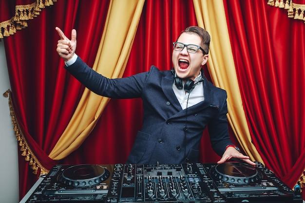 Dj mit einem mixer zeigt seine hände zur seite.