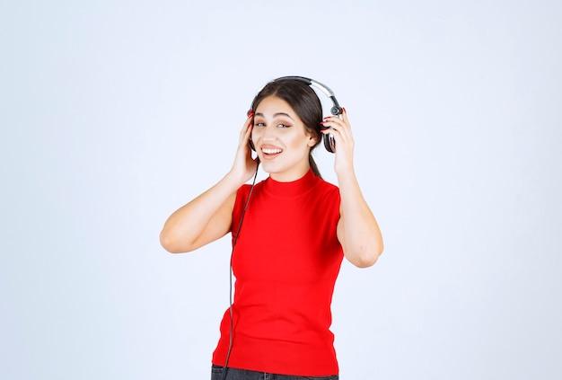 Dj mit kopfhörern, die ein ohr herausnehmen, um gut zu hören.