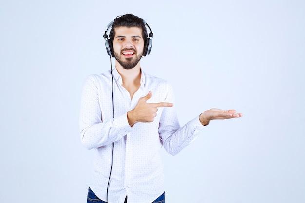 Dj mit kopfhörern, die tanzen und auf jemanden rechts zeigen
