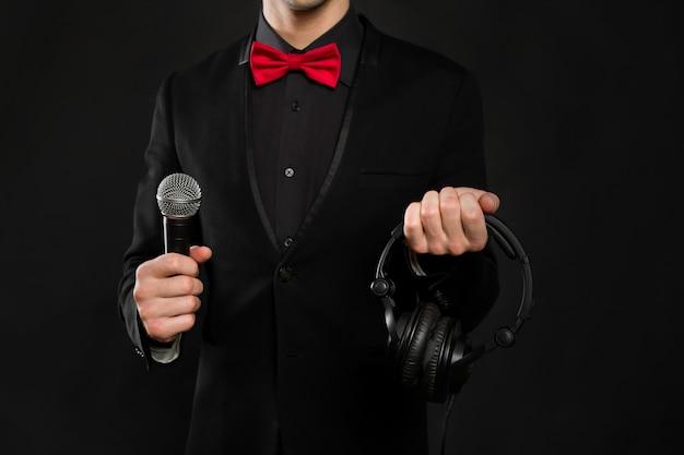 Dj mit kopfhörern und mikrofon an einer schwarzen wand