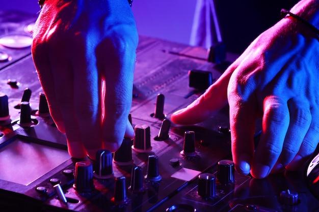 Dj-mixing-tracks auf einem mixer in einem nachtclub