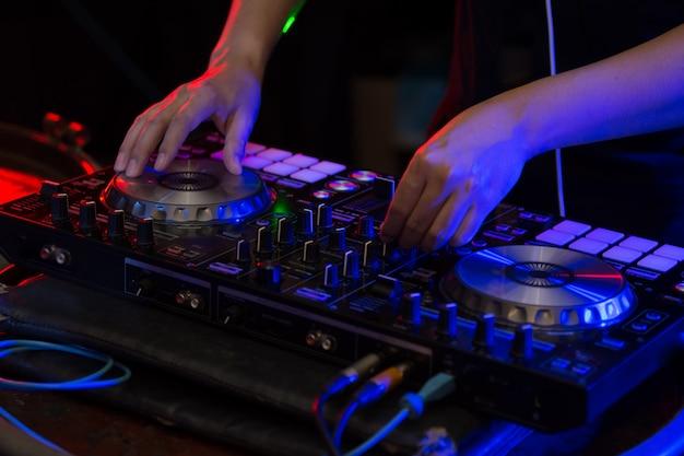 Dj mixing tracks auf einem mixer in einem nachtclub.