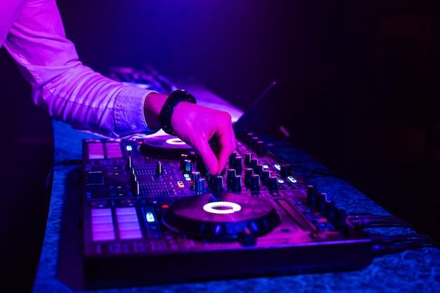 Dj spielt musik mit seinen händen auf einem mixer-controller