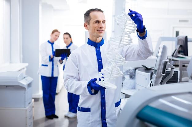Dna-rätsel. wehmütiger glücklicher männlicher wissenschaftler, der dna trägt und nach genort sucht, während er im labor aufwirft