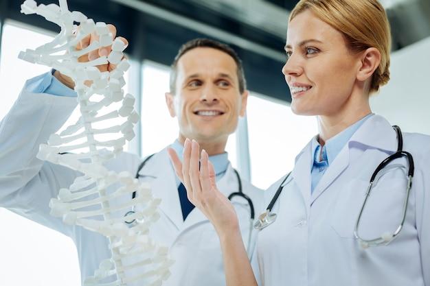 Dna-studien. schöne nette wissenschaftlerin, die zusammen mit ihrer kollegin steht und lächelt, während sie dna studiert