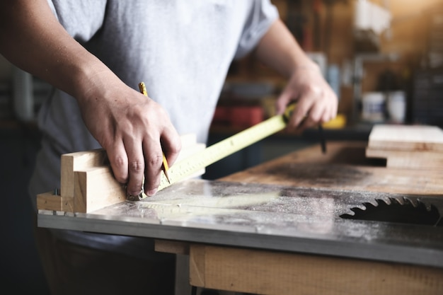 Do-it-yourself-konzept handwerker verwenden ein maßband, um holzteile zu holztischen für kunden zusammenzusetzen.
