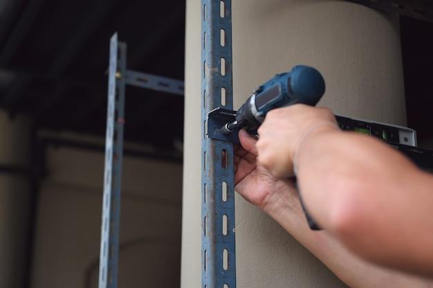 Do-it-yourself-konzept, handwerker verwenden elektrische bohrmaschinen, um alte eisenteile zusammenzubauen. machen sie an ihrem freien wochenende ein regal.
