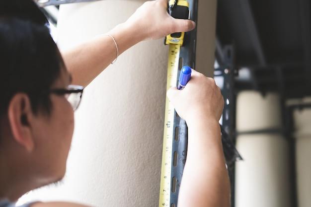 Do-it-yourself-konzept mit höhenmaßbändern bauen handwerker alte eisenteile zusammen. machen sie ein regal für das wochenende.
