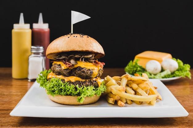 Doble burger mit doble cheddar käse, salat, speck, champignons und pommes frites