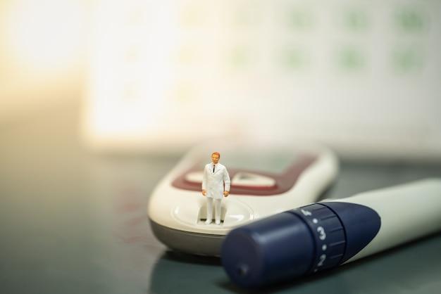Docter miniaturfigur menschen, die auf glukosemessgerät mit lanzette und kalender als hintergrund stehen.