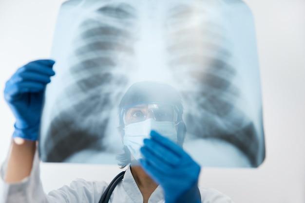 Doctor scientist prüft die untersuchung einer virusinfektion oder einer lungenentzündung auf einem röntgenfilm der brust. coronavirus 2019, covid-19