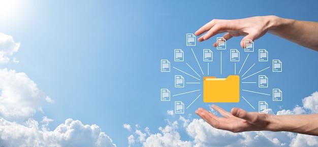 Document management system dms. businessman hold-ordner und dokumentsymbol. software zum archivieren, suchen und verwalten von unternehmensdateien und -informationen. internet-technologiekonzept. digitale sicherheit.