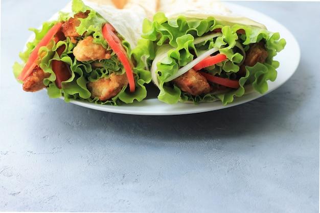 Döner auf einem weißen teller. shawarma mit fleisch, zwiebeln, salat und tomate an auf grauem hintergrund.