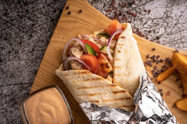 Döner kebab, ein döner in einer grube mit frischem gemüse und fleisch. mit großen gewürzen. restaurant serviert. auf dunklem hintergrund. für menüs und anzeigen
