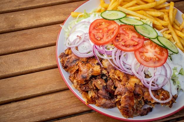 Döner kebab oder gyros auf einem teller mit pommes frites