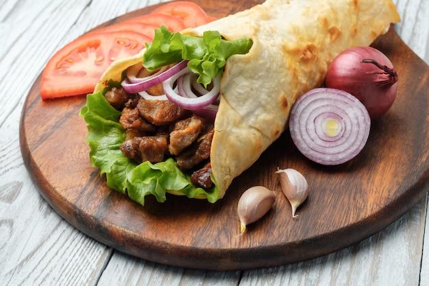 Döner liegt auf dem schneidebrett. shawarma mit fleisch, zwiebeln, salat liegt auf einem weißen alten holztisch.