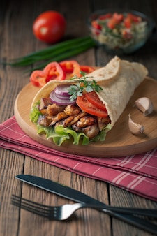 Döner liegt auf dem schneidebrett. shawarma mit hühnerfleisch, zwiebeln, salat liegt auf einem dunklen alten holztisch.