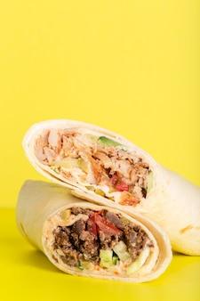 Döner roll shawarma mit hühnchen und gemüse auf gelbem foto von hoher qualität