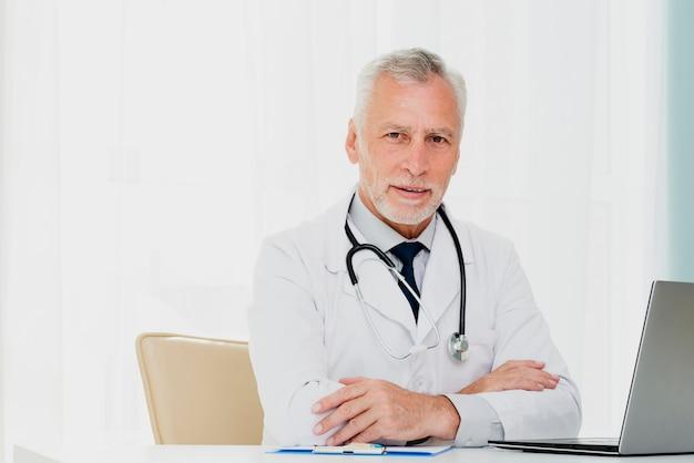 Doktor am schreibtisch, der kamera betrachtet