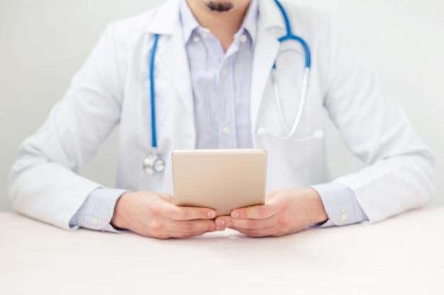 Doktor arbeitet an einem digitalen tablet