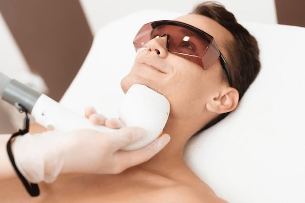 Doktor behandelt seinen hals und gesicht mit einem speziellen apparat