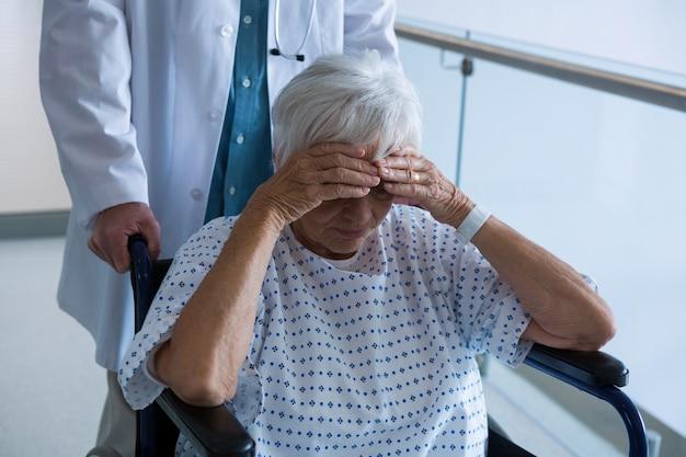 Doktor, der älteren patienten auf rollstuhl im durchgang drückt