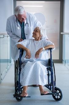 Doktor, der älteren patienten auf rollstuhl im durchgang hält