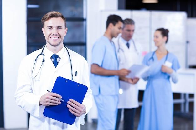 Doktor, der ärztlichen attest hält und während seine kollegendiskussion lächelt