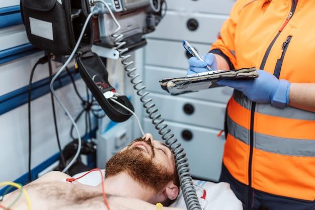 Doktor, der ärztlichen attest zum klemmbrett am krankenhaus, dringlichkeitsraum schreibt. medizin, menschen und gesundheitskonzept.