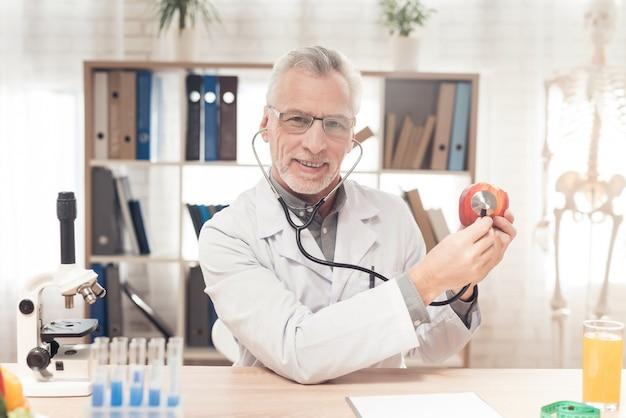 Doktor, der am schreibtisch im büro, hörender apfel sitzt.