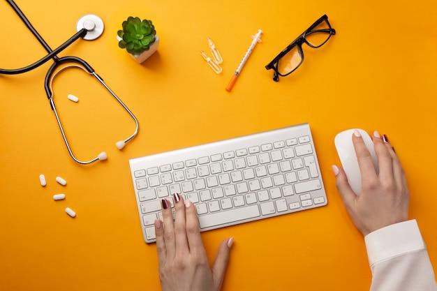 Doktor, der am schreibtisch sitzt und an seinem computer mit medizinischer ausrüstung ganz herum arbeitet