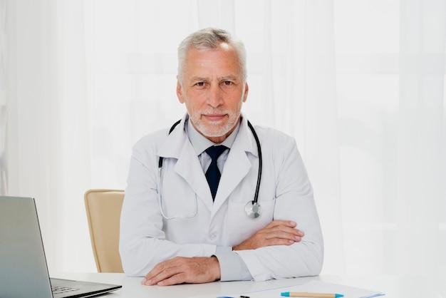 Doktor, der am schreibtisch sitzt