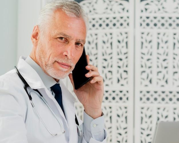 Doktor, der am telefon betrachtet kamera spricht