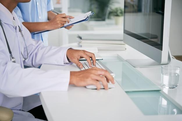 Doktor, der an computer arbeitet