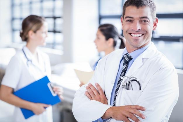 Doktor, der an der kamera im krankenhaus lächelt