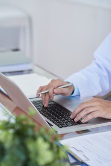 Doktor, der an laptop arbeitet