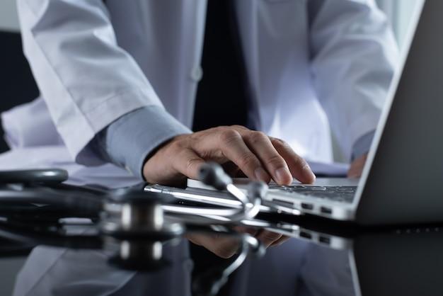 Doktor, der an laptop-computer für medizinisches online-konzept arbeitet